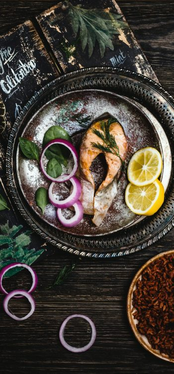 Top view of baked salmon steak with lemon and onion on rustic metal tray with rice side dish on dark
